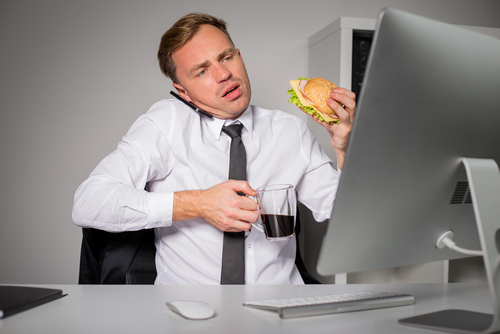 busy man eating burger and coffee in front of work computer