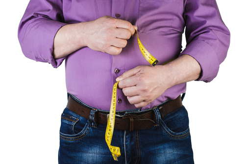 overweight guy measuring waist