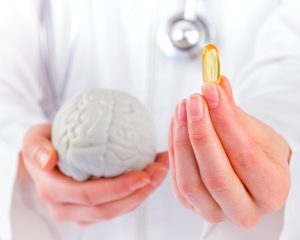 doctor holding brain model and nootropic supplement