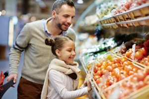 father doing errands with daughter at grocery store