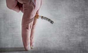 Holding cigarette between fingers depicting erectile dysfunction