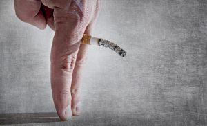 Holding cigarette between fingers depicting erectile dysfunction