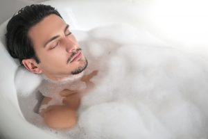 man soaking in hot bath