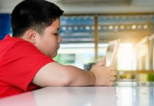 obese child on social media on his tablet