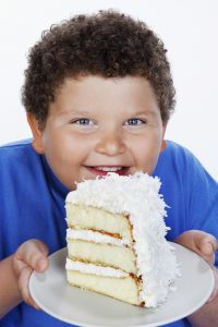 fat kid holding a big slice of cake child obesity