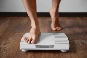 man who takes Progentra stepping on weighing scale