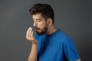man checking for his breath odor