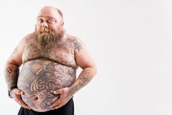 obese bearded man with tattoos holding his belly