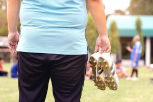 obese man standing in football field holding his shoes